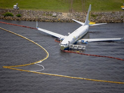 Containment and absorbent booms surround a Boeing 737 aircraft in the St. Johns River after the aircraft slid off the runway at Naval Air Station Jacksonville, May 3, 2019. All 143 passengers aboard the flight from Naval Station Guantanamo Bay, Cuba were rescued. (Mass Communication Specialist 3rd Class Thomas A. Higgins/Navy)