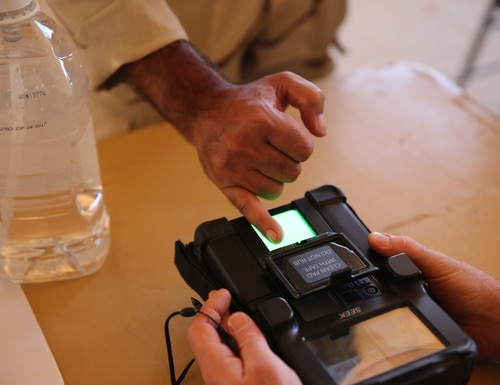 A soldier with the 7th Iraqi Army Division scans his fingerprint during a military training enrollment at Al Asad Air Base, Aug. 17, 2015. The enrollment processes administrative and biometric data for the Iraqi soldiers before beginning a six-week build partner capacity course focusing on small unit tactics and infantry skills. The biometric enrollment is a critical part of the course as it allows coalition forces to maintain accountability of soldiers and their equipment during the training. (U.S. Marine Corps photo by Cpl. Garrett White/Released)