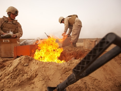 Marines dispose of trash in a burn pit in Khan Neshin District in Afghanistan in March 2021. (Cpl. Alfred V. Lopez/Marine Corps)