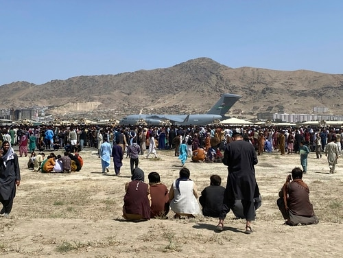 Hundreds of people gather near an Air Force C-17 transport plane Monday at the perimeter of the international airport in Kabul, Afghanistan. Thousands are getting out daily, but far fewer than the Air Force is able to carry. (AP Photo/Shekib Rahmani/AP)
