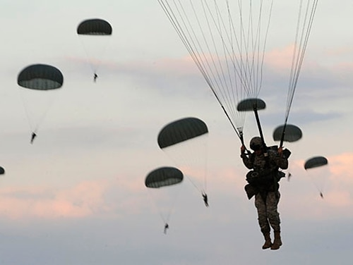Soldiers from the 82nd Airborne Division parachute after jumping from a C-130 Hercules aircraft over Fort Bragg, North Carolina. The division shut down the connection between the storied paratroopers and a white supremacist. (Staff Sgt. Elizabeth Rissmiller/Air Force)
