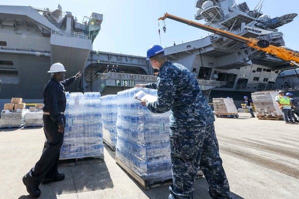 Sailors assigned to the Nimitz-class aircraft carrier USS Abraham Lincoln (CVN 72) move cases of water on Sept. 7, 2017, during a supply onload in Norfolk, Va. (MC3 Patrick D. Maher/Navy)