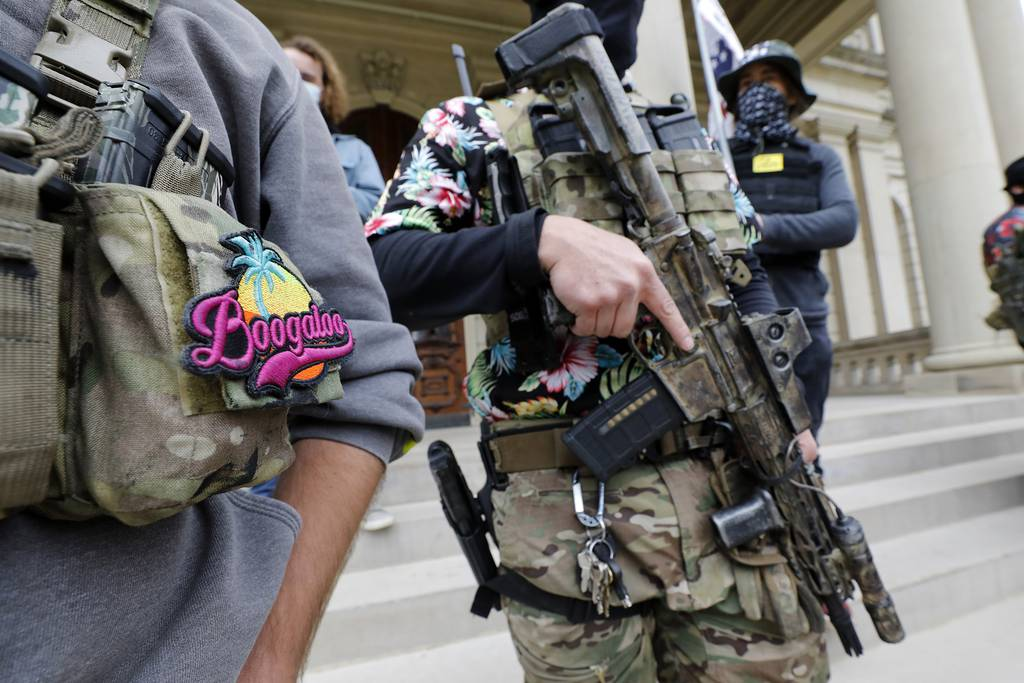 A group tied to the Boogaloo Bois holds a rally as they carry firearms at the Michigan State Capitol in Lansing, Mich., on Oct. 17, 2020.