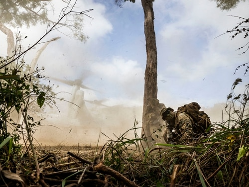 U.S. Marines shield themselves from dust as an MV-22 Osprey tiltrotor aircraft takes off from Shoalwater Bay Training Area in North Queensland, Australia, July 19, 2017, during Exercise Talisman Saber 17. More than 500 U.S. Marines and Australian soldiers landed ashore at Freshwater Beach in Central Queensland . during simulated amphibious assault landings during the exercise. (Royal Australian Navy photo by Leading Seaman Imagery Specialist Jake Badior)