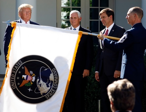 Former President Donald Trump announced in August 2019 the creation of U.S. Space Command, watching with former Vice President Mike Pence and then-Defense Secretary Mark Esper as the command's flag is unfurled in the Rose Garden of the White House. (Carolyn Kaster/AP)