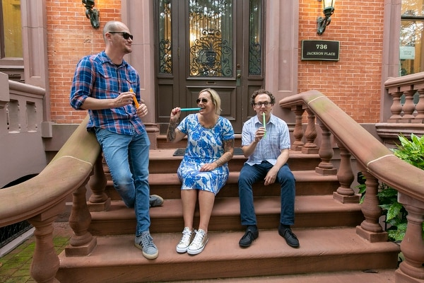 Scott Haselton, digital service expert (at left), Shannon Sartin, executive director of digital services for the Department of Health and Human Services (center), and Sam Gensburg, digital service expert (right), take a break to enjoy freeze pops on the front steps to the U.S. Digital Service. (Alan Lessig/Staff)