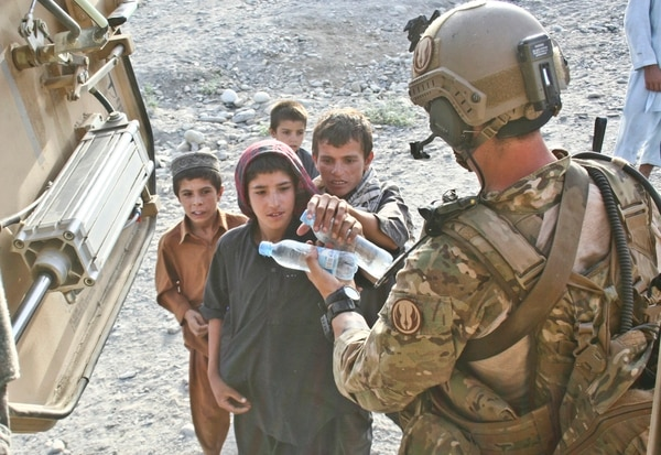 An Air Force JTAC offers Afghan children bottles of water after completing a mission in Khanda village, Laghman province, Afghanistan. (Army)