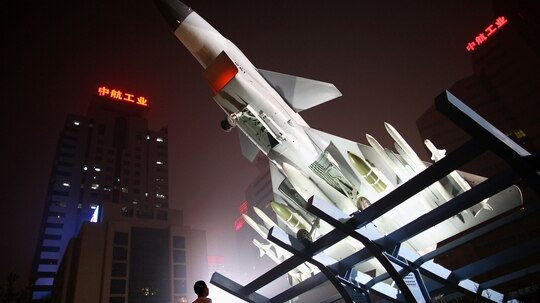 A man looks up at a Chinese J-10 fighter jet outside the office of Aviation Industry Corporation of China on Sept. 2, 2009, in Beijing, China. (Feng Li/Getty Images)