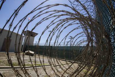 In this April 17, 2019, file photo reviewed by U.S. military officials, the control tower is seen through the razor wire inside the Camp VI detention facility in Guantanamo Bay Naval Base, Cuba.