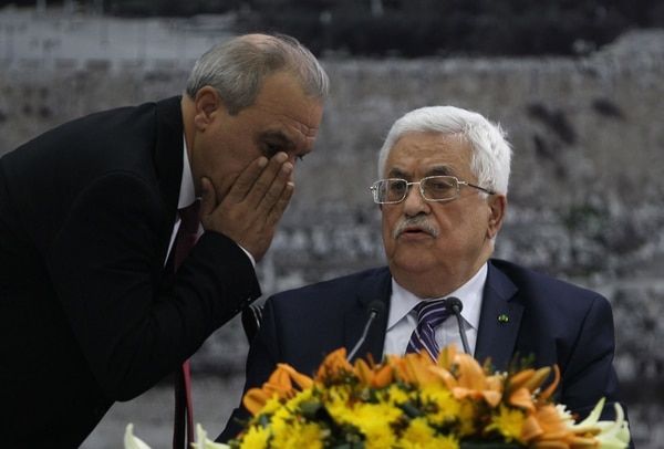 Director of Palestinian General Intelligence in the West Bank Majid Faraj (L) whispers to President Palestinian president Mahmud Abbas during a meeting where he requested to join 15 United Nations agencies, abandoning pledges to refrain from doing so during nine months of talks that were to end April 29, at his headquarters in the West Bank city of Ramallah on April 1, 2014. AFP PHOTO / ABBAS MOMANI (Photo credit should read ABBAS MOMANI/AFP/Getty Images)