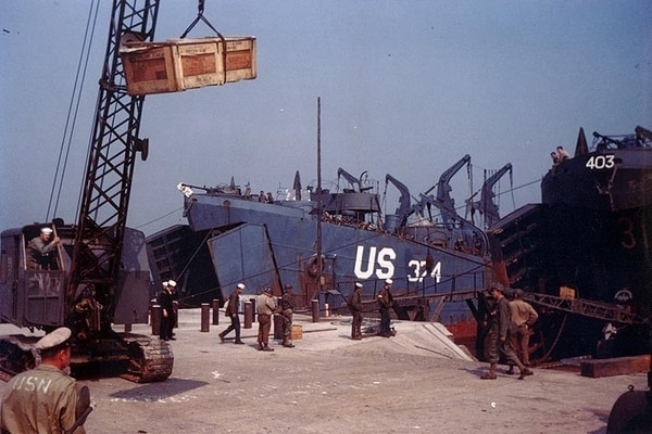 A mobile crane lifts a crate during pre-invasion loading in an English port, circa late May or early June 1944. USS LST-374 (center) and USS LST-314 (extreme right) are at the ramps in the background. LST-314 was sunk by German motor torpedo boats on 9 June 1944. (National Archives)