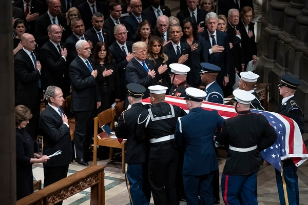 The flag-draped casket of former President George H.W. Bush is carried by a military honor guard past former President George W. Bush, President Donald Trump, first lady Melania Trump, former President Barack Obama, Michelle Obama, former President Bill Clinton, and former Secretary of State Hillary Clinton, at the conclusion of a State Funeral at the National Cathedral, Wednesday, Dec. 5, 2018, in Washington. In the second row are Vice President Mike Pence, and his wife Karen Pence, former Vice President Dan Quayle, and his wife Marilyn Quayle and former Vice President Dick Cheney. (Carolyn Kaster/AP)