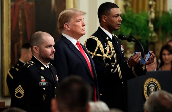President Donald Trump stands as the citation is read during a ceremony to award the Medal of Honor to former Staff Sgt. Ronald Shurer II, left, for actions in Afghanistan. The ceremony took place in the East Room of the White House, Oct. 1, 2018. (Evan Vucci/AP)