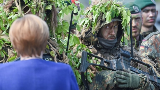 German Chancellor Angela Merkel talks to soldiers of the German armed forces, Bundeswehr, during an educational practice of the