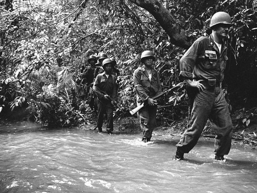 A United States advisor and a Vietnam company commander lead troops through an open area of swamp in jungles about 25 miles east of Saigon on Oct. 25, 1962. (Horst Faas/AP)