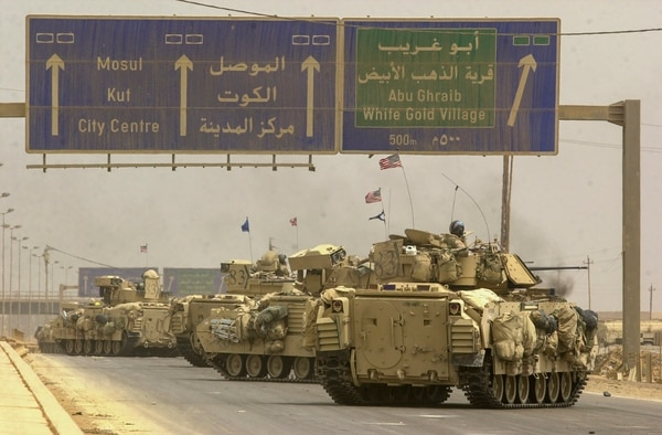 Vehicles from the Army's 3rd Infantry Division move to the northwestern side of the city to complete the encirclement of Baghdad, Iraq, during the early days of the war. (Warren Zinn/Staff)