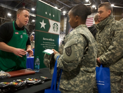 IMAGE DISTRIBUTED FOR U.S. CHAMBER OF COMMERCE FOUNDATION - Starbucks recruiter and Air Force veteran Afsheen Saatchi, left, talks with Spc. Shaquille Armstrong, center, during the Washington State Service Member for Life Transition Summit Job Fair on Thursday, Oct. 23, 2014 at Joint Base Lewis-McChord, Wash. The three-day summit is held in partnership with the U.S. Chamber of Commerce Foundation's Hiring Our Heroes program, the U.S. Department of Veterans Affairs, the U.S. Department of Labor, the U.S. Department of Defense, Camo 2 Commerce, and the U.S. Army. Sponsored by Starbucks, Amazon, Call of Duty Endowment, First Data, Toyota, University of Phoenix, USAA and Verizon, the event is part of a series of collaborative efforts between the public and private sectors to connect veterans, transitioning service members, and military spouses to meaningful employment opportunities. The event culminated with a Hiring Our Heroes job fair with more than 4,500 service members, veterans, and military spouses. (Stephen Brashear/AP Images for U.S. Chamber of Commerce Foundation)
