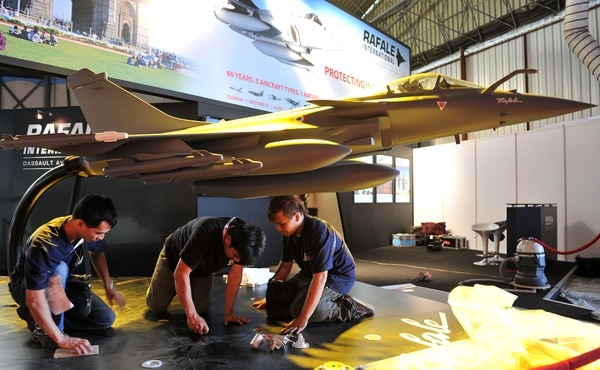 Indian workers at a Rafale fighter jet stall prepare an aircraft model ahead of the 9th edition of Aero India 2013 at the Yelahanka Air Force station in Bangalore on February 5, 2013. The 5-day event starting from January 6 will be inaugurated by Indian defence minister AK Antony and is a major platform for foreign vendors. The biennial event is crucial to international participants and investors at a time when the Indian government is set to spend USD 100 billion in the defence sector within the next five years. AFP PHOTO/Manjunath KIRAN (Photo credit should read Manjunath Kiran/AFP/Getty Images)