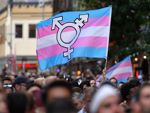 A person holds a transgender pride flag at a rally in New York. A transgender naval officer was just granted a waiver to remain in the service (Angela Weiss/AFP via Getty)