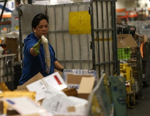 The U.S. Postal Service has reduced employee compensation costs over the last decade, but not as much as the agency initially predicted. (Justin Sullivan/Getty Images)