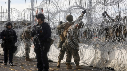 U.S. Customs and Border Protection agents, left, stand watch as U.S. Marines handle concertina wire at the San Ysidro port of entry Nov. 22, 2018 in Tijuana, Mexico. President Trump suggested in a Dec. 11 tweet that U.S. troops should finish building the border wall. (Mario Tama/Getty Images)