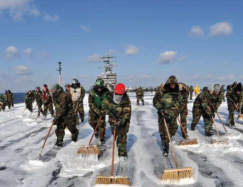 Sailors aboard the aircraft carrier USS Ronald Reagan conduct a countermeasure wash down on the flight deck. Sailors scrubbed the external surfaces on the flight deck and island superstructure to remove potential radiation contamination. Ronald Reagan is operating off the coast of Japan providing humanitarian assistance as directed in support of Operation Tomodachi.(U.S. Navy photo by Seaman Nicholas A. Groesch)