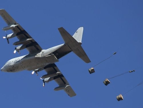 A KC-130T from Marine Aerial Refueler Transport Squadron 452 drops cargo as part of container delivery system training at a drop zone on Camp Lejeune. (Lance Cpl. Ashley McLaughlin/Marine Corps)