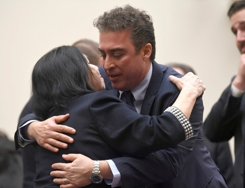 Christine Levinson, left, wife of Robert Levinson, a former FBI agent who vanished in Iran in 2007, gets a hug from Babak Namazi, right, the son of Baquer Namazi who has been held in Iran. (Susan Walsh/AP)