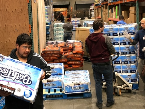 Shoppers rush to pick up toilet paper that had just arrived at a Costco store on Saturday in Tacoma, Wash. Within minutes, several pallets of toilet paper and paper towels were sold out as people continue to stock up on necessities due to fear of the COVID-19 coronavirus. (Ted S. Warren/AP)