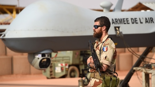 A French soldier involved in the regional anti-insurgent Operation Barkhane stands guard next to a Reaper drone at the French military air base in Niamey on March 14, 2016. (Pascal Guyot/AFP via Getty Images)