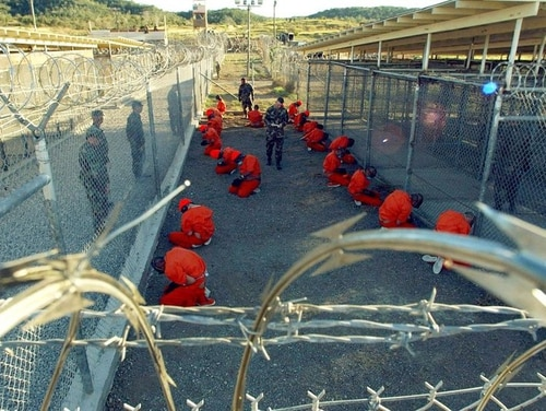 Detainees in orange jumpsuits sit in a holding area under the watch of U.S. military police at the temporary Camp X-Ray, which was later closed and replaced by Camp Delta, inside Guantanamo Bay naval base.(Handout/Reuters)