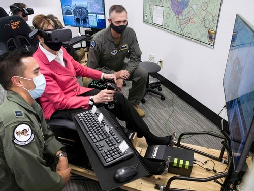 Next, Secretary of the Air Force Barbara Barrett uses a virtual reality flight simulator as Captain Orion Kellogg, left, and Maj. Gen. Craig Wills, commander of the 19th Air Force, observe during his August 2020 visit to Undergraduate Pilot Training 2.5 at Joint Base San Antonio Randolph, TX.  (Sean M. Worrell / Air Force)
