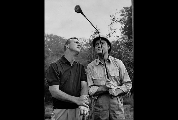 American golfer Arnold Palmer, left, and entertainer Bob Hope (1903 - 2003) examine a bent golf club during the filming of
