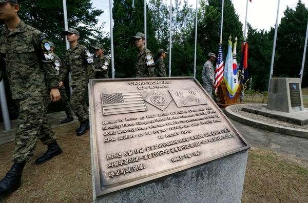In this Aug. 16, 2013, file photo, South Korean and U.S. soldiers walk by the Camp Bonifas naming information during the 37th Barrett-Bonifas memorial ceremony at the Camp Bonifas near the border village of Panmunjom, which has separated the two Koreas since the Korean War. Two U.S. Army officers, Capt. Arthur Bonifas and Lt. Mark T. Barrett, were killed by axe-wielding North Korean border guards at the truce village of Panmunjom on Aug. 18, 1976. (Lee Jin-man/AP)