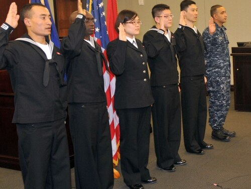 The first Navy sailors to participate in the defense secretary's Military Accessions Vital to National Interest pilot program are issued the oath of citizenship by an official with the U.S. Citizenship and Immigration Services Chicago field office. MAVNI was designed to recognize foreign nationals with skills considered to be vital to national interest such as doctors, nurses and certain language experts and give them the opportunity to expedite the naturalization process by serving in the U.S. military. (Scott Thornbloom)