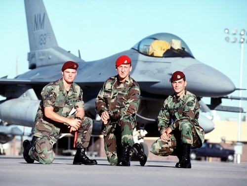 US Air Force Staff Sergeant Jeremy Hardy (right), a pararescueman, US Air Force Senior Airman Ron Ellis (left) and US Air Force Staff Sergeant Andy Kubik (center), a combat controller, members of a rescue team, pose in front of an F-16 Fighting Falcon aircraft at Hurlburt Field, Florida. This image is from the February 2000 Airman Magazine article
