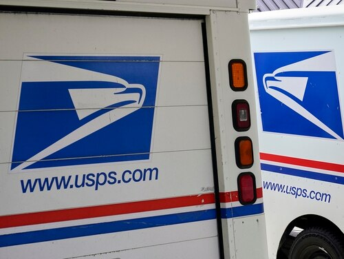 In this Aug. 18, 2020, file photo, mail delivery vehicles are parked outside a post office in Boys Town, Neb. (Nati Harnik/AP)