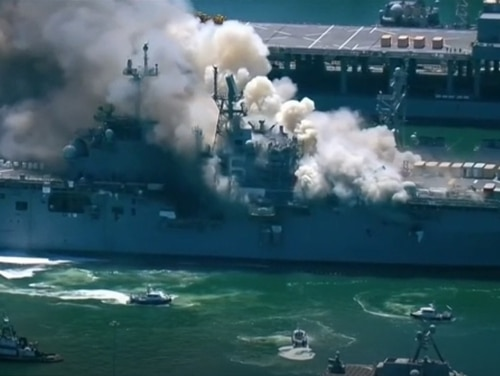 The U.S. Navy ship Bonhomme Richard is shown at Naval Base San Diego, Calif., on July 12, 2020, after an explosion and fire onboard the ship. The Chief of Naval Operations said the damage was made worse by wind and explosions. (KGTV-TV via AP)