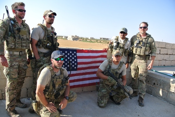 The Special Operations Surgical Team during a reenlistment. Standing at back, left to right, emergency medicine physician Lt. Col. Ben Mitchell, emergency room nurse Capt. Cade Reedy, emergency room nurse Maj. Nelson Pacheco, nurse anesthetist Lt. Col. Matthew Uber. Kneeling, surgeon Maj. Justin Manley, left, and respiratory therapist Tech. Sgt. Richard Holguin, right. (Air Force)