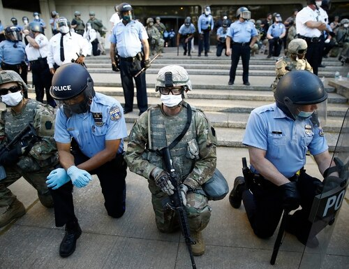 In this June 1, 2020, file photo, Philadelphia police and Pennsylvania National Guard take a knee at the suggestion of Philadelphia Police Deputy Commissioner Melvin Singleton, unseen, outside Philadelphia Police headquarters in Philadelphia, during a march calling for justice over the death of George Floyd. (Matt Rourke/AP)