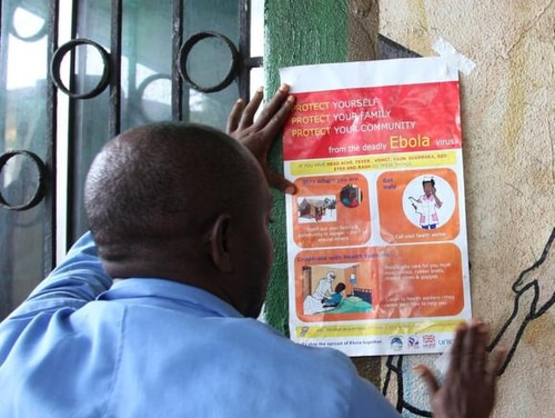 A nurse sets an information sign about Ebola on a wall of a public health center on July 31, 2014 in Monrovia. Liberia announced on July 30 it was shutting all schools and placing
