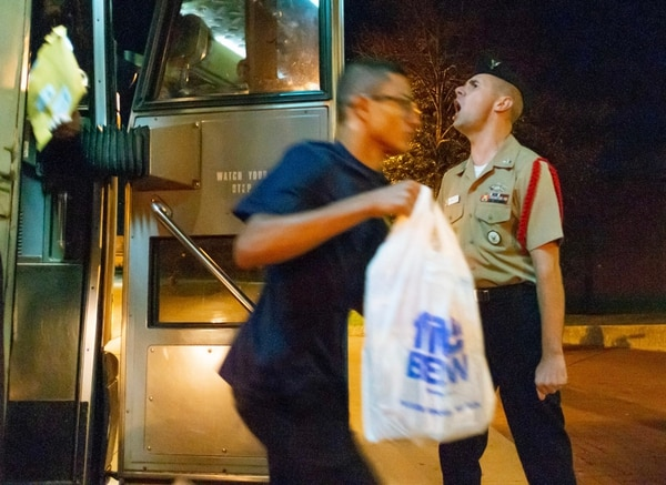 """Construction Mechanic 1st Class (SCW) Jeremy Pratt greets recruits as they get off the bus from Chicago O'Hare International Airport during a """"Night of Arrival."""" (Mark D. Faram/Staff)"""