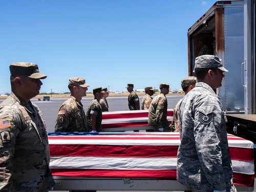 Servicemembers with the Defense POW/MIA Accounting Agency load cases containing remains of unidentified U.S. troops for transport during an honorable carry ceremony at Joint Base Pearl Harbor/Hickam in Hawaii on June 19. (Sgt. Julian Temblador/Marine Corps)