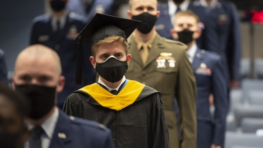 Nathan R. Boone and his classmates take their seats at the start of the Air Force Institute of Technology graduation ceremony March 25 at Wright-Patterson Air Force Base, Ohio. Approximately 250 advanced degrees were awarded to airmen and Space Force guardians. (R.J. Oriez/Air Force)