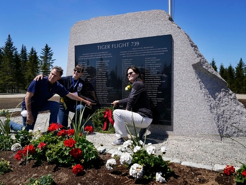John Williams, of Peru, Ind., left, and his sisters, Maria McCauley, of Branson, Mo., center, and Susie Linale, of Omaha, Neb., pose at a monument to honor the military passengers of Flying Tiger Line Flight 739, Saturday, May 15, 2021, in Columbia Falls, Maine. Their father, SFC Albert Williams Jr., was among those killed on the secret mission to Vietnam in 1962. (Robert F. Bukaty/AP)