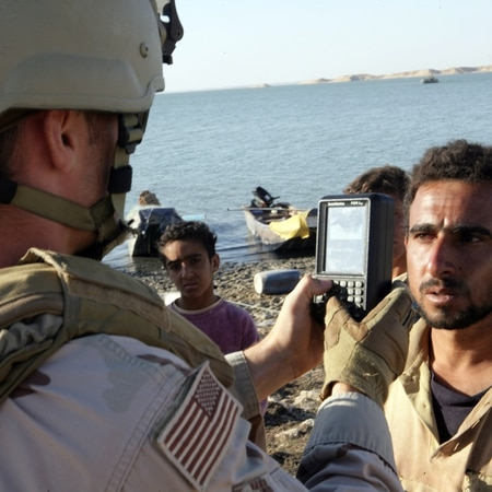 A boy watches as Petty Officer 2nd Class Shawn Sass, assigned to Riverine Squadron 3, performs a biometrics scan on a fisherman on the Watah peninsula, near Rawah, Iraq. Riverine units are actively engaged in waterborne operations in Anbar province to update census details, improve security and deter insurgent activity.