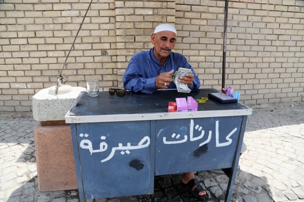 In this Saturday, Aug. 8, 2015, photo an Iraqi street currency exchanger counts banknotes in Baghdad, Iraq. Iraq is battling both the Islamic State group and massive budget deficits brought on by the lowest global oil prices in six and a half years, forcing it to cut spending on government projects local businesses have relied on for years. (AP Photo/Karim Kadim)