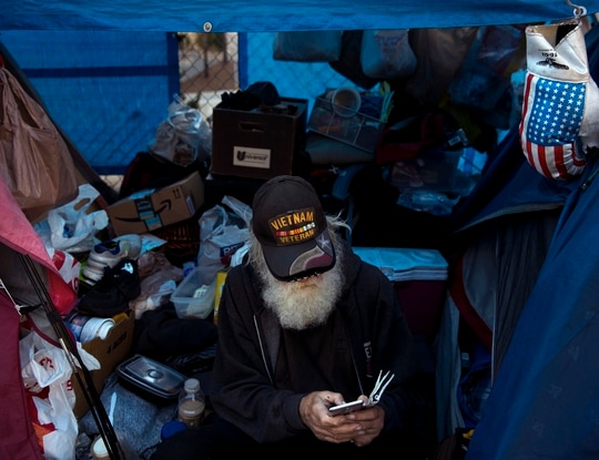 Theodore Neubauer, a 78-year-old Vietnam War veteran who is homeless, looks at his smartphone while sitting in his tent on Dec. 1, 2017, in Los Angeles. (Jae C. Hong/AP)