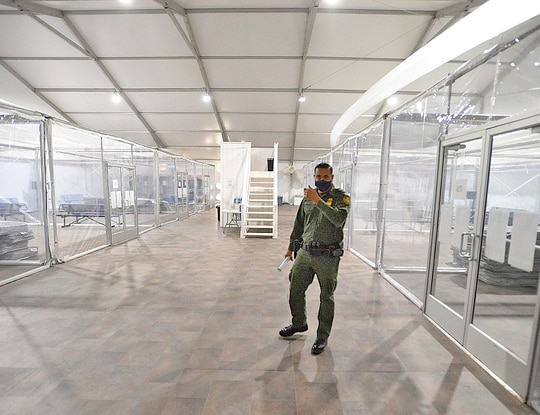 U.S. Border Patrol Yuma Sector Agent Fidel Cabrera leads a tour of one of four living areas inside Yuma Sector's Processing Facility during an open house on April 20, 2021. (Randy Hoeft/The Yuma Sun via AP)