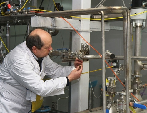 An unidentified International Atomic Energy Agency inspector disconnects the connections between the twin cascades for 20 percent uranium production at nuclear power plant of Natanz, south of Tehran, Iran, on Jan. 20, 2014 (Kazem Ghane/AFP via Getty Images)